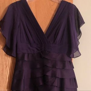 Purple dress below the knee with layers.